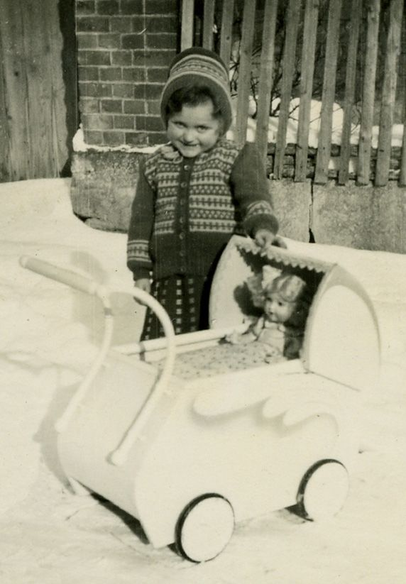 A young Canadian girl is photographed with her doll and play pram during snow season, c. 1950s.