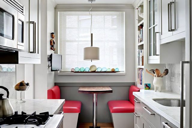 breakfast nook with red vinyl banquette bench seating and small galley kitchen with shaker cabinets, marble counter, and fisherman float bal...