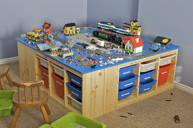 """LEGO Table  from IKEA. The bins (also from IKEA) are made to slide into all the nice slots.    The table top is made from a 5' x 5' piece of baltic birch plywood cut to 4' 8"""". I rounded the corners of the top, routed 1/8"""" edge, and sanded it using an orbital sander.  spray paint which matched the blue LEGO color exactly, and then a clear coat) bought from Home Depot."""