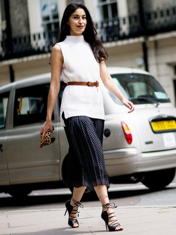 Caroline Issa wears a belted sleeveless sweater over a midi skirt, and accessorizes with a printed zip pouch and lace-up heels