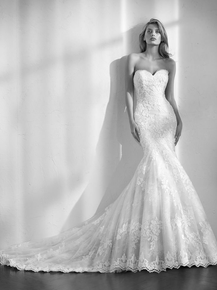 Incroyable robe de mariée à coupe sirène en dentelle de Chantilly et en tulle ornée de fantaisies de pierres fines. Une robe qui épouse le corps en mettant la silhouette en valeur. La jupe épouse les hanches et s'ouvre sur une jupe basse vaporeuse confectionnée en couches de tulle. Une robe à décolleté en cœur et dos nu qui associe un empiècement amovible en tulle cristal orné d'applications de broderie au fil et de pierres fines.
