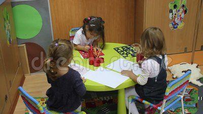 Preschoolers to kindergarten during educational activities - little girls drawing with crayons.