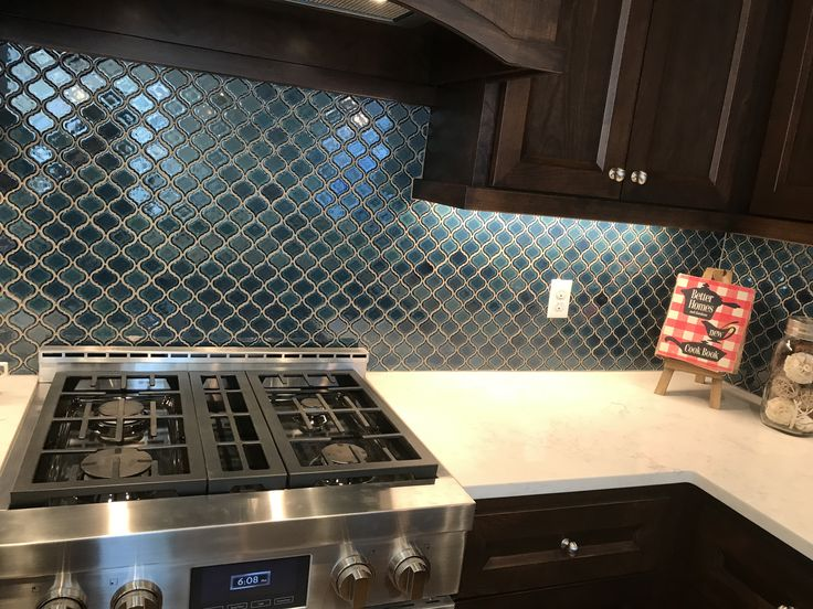"Brilliant teal lantern tile adorns this kitchen backsplash. Designer: Nicole Fisher. Photographer: Olivia Hettrich. 2017 Street of Dreams ""Nevaeh"" by Paulson's Floor Coverings."