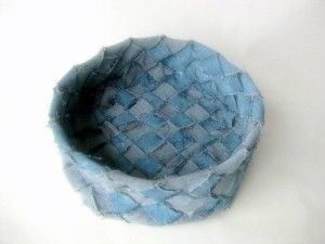 """From the Website: """"This rustic basket is woven/plaited with strips cut from recycled blue jeans.  During weaving the basket the soft fabric strips took on an organic life of their own, adding to the relaxed look. The basket has been treated with diluted acrylic paint to stiffen the surfaces making the basket firm to the touch. The basket is woven using an old Scandinavian basket weaving technique."""""""