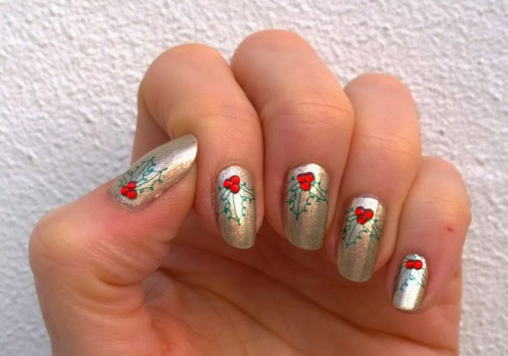 Sanne's Christmas nails: stamped holly leaves and added red rhinestones on a cheap gold polish, 2014.