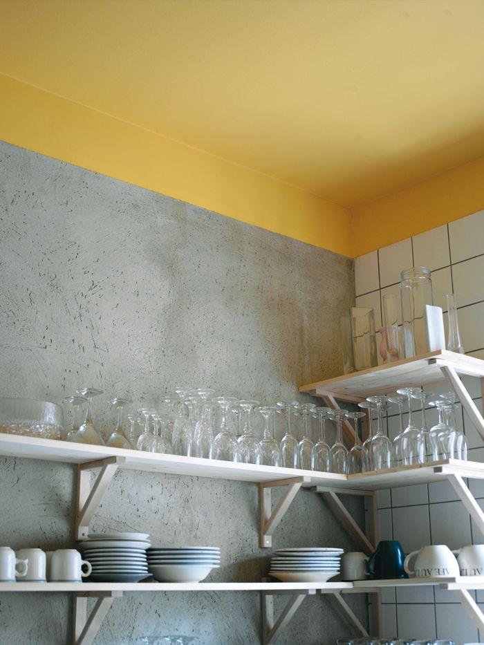 Gult tak och betongvägg ger effektfullt möte mellan materialen. Öppna hyllor från Ikea.