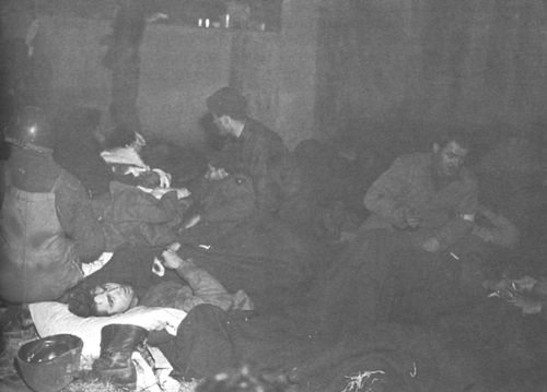 CASUALTIES IN AN IMPROVISED EMERGENCY WARD during the siege of Bastogne. Belgium 1944