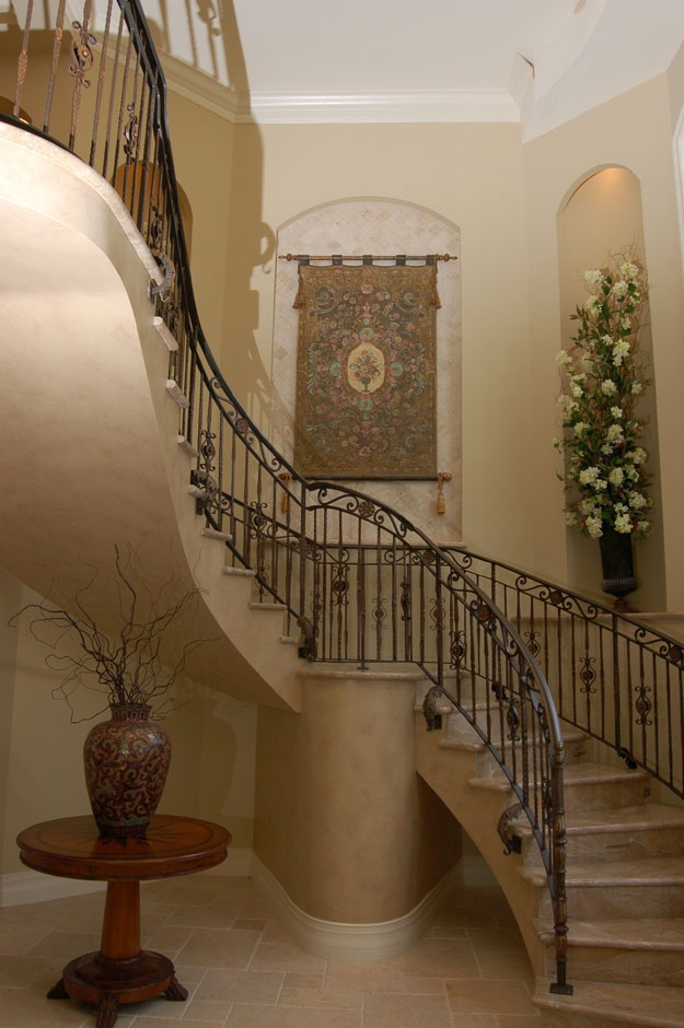 Elegant staircase in the foyer of this home spanish for House plans with stairs in foyer