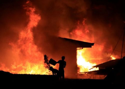 Photos of the day - February 8 2017 Resident throws a bucket of...  Photos of the day - February 8 2017  Resident throws a bucket of water at burning shanties at a community of informal settlers engulfed by a fire in Catmon Malabon city metro Manila; Kaique Marcelo Albuquerque is comforted during the funeral of his father policeman Mario Marcelo Albuquerque who was killed in the line of duty in Serra Espirito Santo Brazil; Lydia Lassila of Australia performs an aerial during an Aerials…