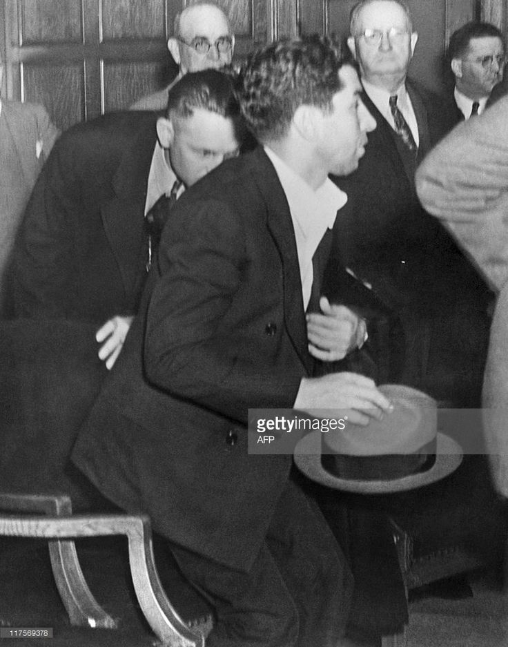 Picture released on April 8, 1936 of alleged 'king in Arkansas' Charles 'Lucky' Luciano (holdind his hat), Italian gangster rising in front of deputy sheriffs, during a hearing in Arkansas Governor J. Marion Futrell office, for extradition to New York to face trial on Mafia crime families, prostitution, Heroin traffic and multitude of charges.