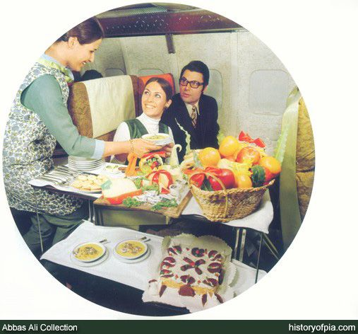 In-flight meals service for First Class passengers aboard Pakistan International Airlines (PIA) Boeing jetliner in early 1970s.  The flight attendant is wearing uniform designed by French fashion designer Pierre Cardin.