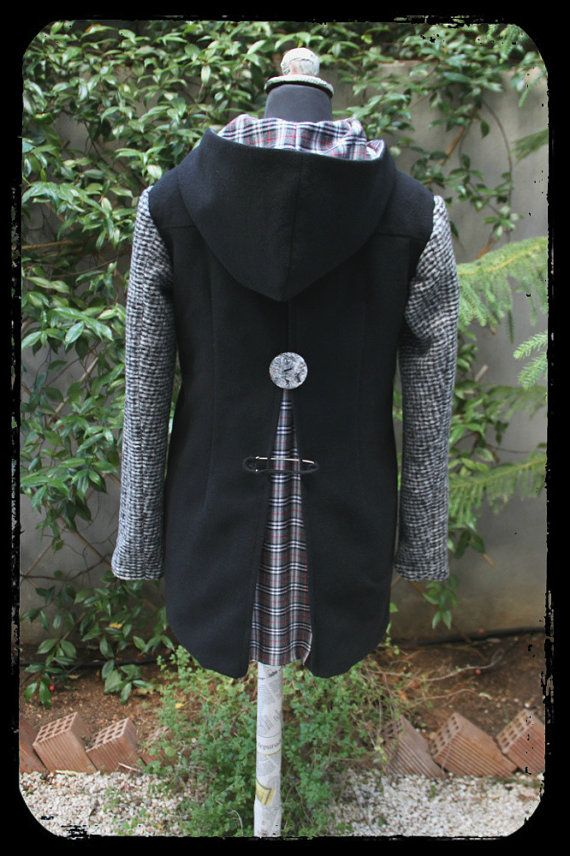 "Black wool coat with grey sleeves, grey coconut buttons and a large handmade crochet pin brooch on the pleat on the back , by ""Eating the Goober"""