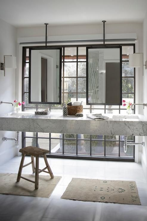 Beautiful transitional bathroom boasts a floating double marble washstand fitted with two undermount sinks accented by wall mounted faucets as two ceiling hung black framed mirrors are positioned in front of a floor-to-ceiling factory window illuminated by two nickle sconces pointed towards staggered white tile floors covered with two small tan bathroom rugs.