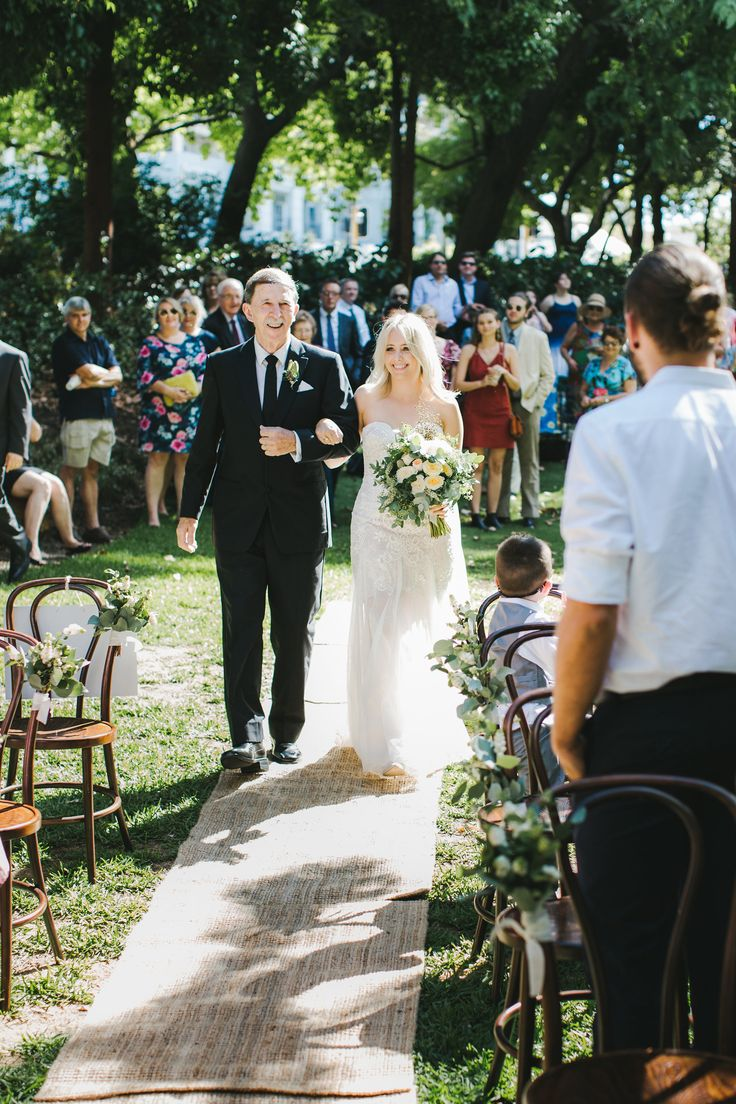 DY.o events (aka Duo) Father and bride walk down the aisle in a summer outdoor ceremony. Sisal aisle runner and timber bentwood stools.