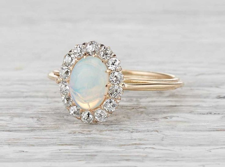 Vintage Victorian ring made in 18k yellow gold and centered with an approximately .75 carat cabochon opal. Accented with old mine diamonds weighing approximately .40 carats total. Circa 1890. Nothing