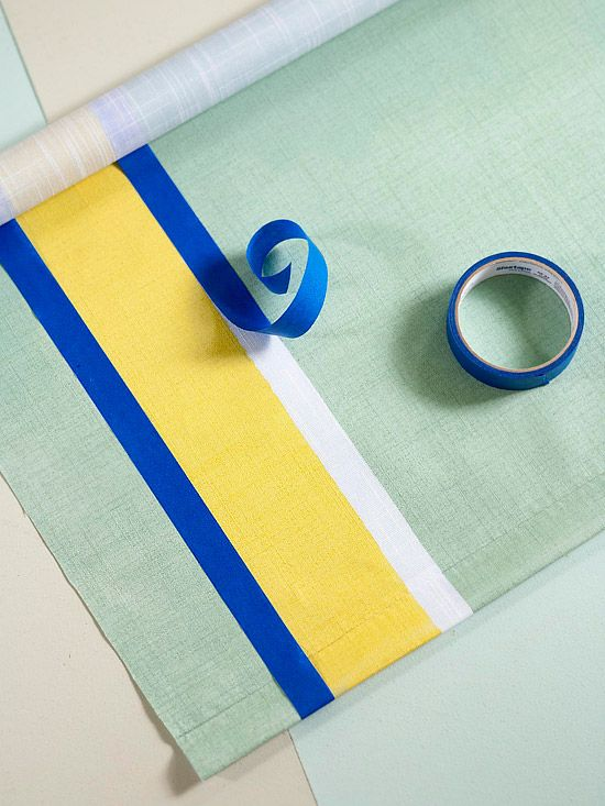 White vinyl roller shades can be painted. Tape off stripes on a plain window shade. Next, press tape edges to seal. Apply latex paint with a foam roller, remove tape immediately, and let dry.
