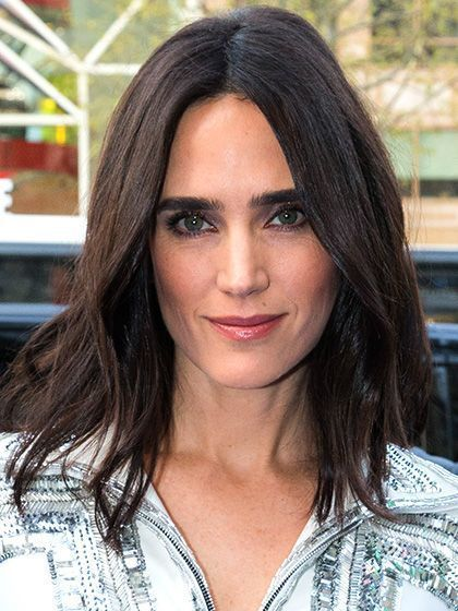 Jennifer Connelly with full eyebrows, barely-there waves, bronzed cheeks and glossy lips | allure.com