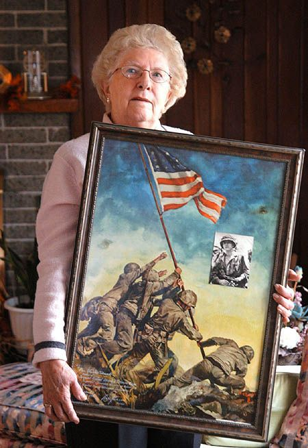 Mary Pero-Strank, sister of the late Marine Sgt. Mike Strank, one of the Iwo Jima flag raisers, holds an oil painting of the Joe Rosenthal photo that captured the famous World War II event.  Pittsburgh Post-Gazette