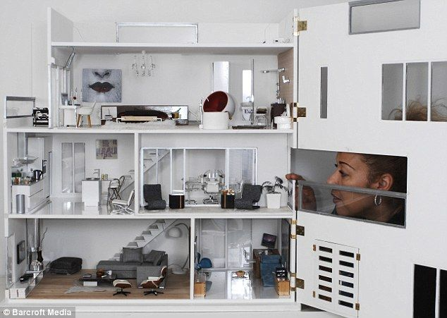 Elaine peers through the front of her modern dolls house, which opens to reveal all of the rooms and hand-made furniture inside