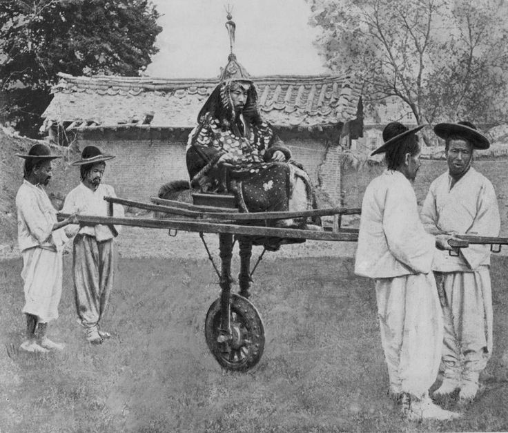 """A nobleman is carried on a litter by four bearers, Korea, circa 1900"""