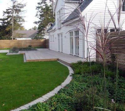 villaträdgård trädäck vid rund gräsmatta