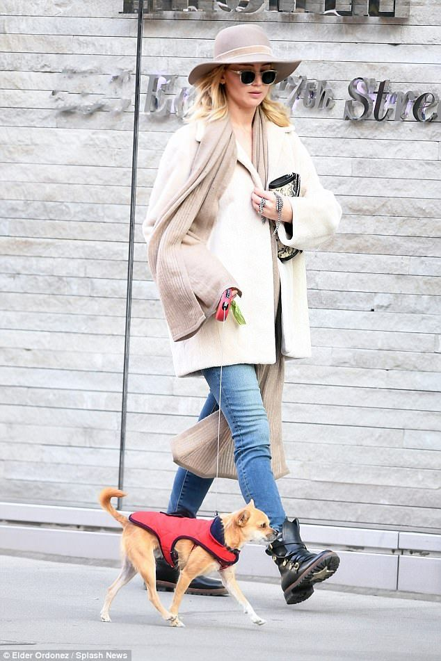 On the go: Jennifer warded off the northeastern chill in a chic off-white coat, stringing ...