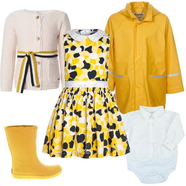 Elegante abito giallo, bianco e blu, con gonna ampia e fascia in vita. sopra ad un body a camicia bianco. Cardigan bianco, con cinta lunga annodata di lato, che riprende la colorazione del vestito. Anti pioggia l' impermeabile giallo con stivali di gomma abbinati.