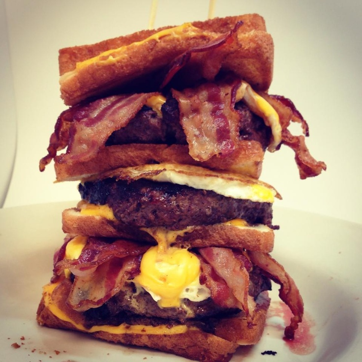This is (and I'm quoting the menu here) the 'Quadruple Coronary Bypass'.  4 grilled cheese sandwiches 3 1/2-lb  burgers, 12 pieces of bacon, 3 eggs and 9 more slices of cheese (21 slices total).  From The Vortex in Atlanta, GA.