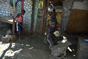 Removing mud from a home damaged by Hurricane Matthew in Jérémie, Haiti