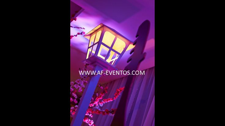 Faroles con luz cálida al inicio del ingreso del salón cerca a la góndola de dulces y a los árboles de flores tono rosa