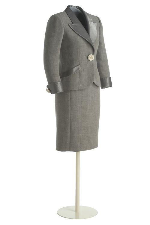 Pertegaz: Traje chaqueta (1998) Tafetán de lana gris jaspeado, hilos de lamé de plata.Chaqueta corta y entallada.Hojas, solapas, cuello, puños vueltos y bolsillos redondeados.Cierre delantero en centro con botón en flor, enfilado de perlas,centro de metal blanco y cristales facetados; botón y ojal cerrando cada puño. Forro de tela gris,botones de nácar gris en hoja dch y presillas en izq.Falda recta a rodilla, cinturilla y abertura bajo espalda.Forro de seda gris, cremallera y corchetes…