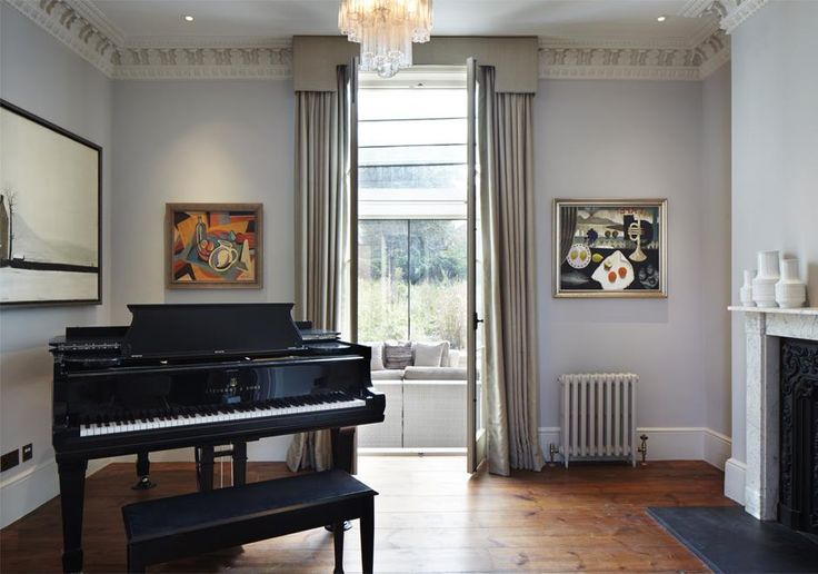 This beautiful room in a listed terraced house in London has tastefully been refurbished keeping the original details while adding modern art and a grand piano. The large glazed doors lead out into the new extension beyond.