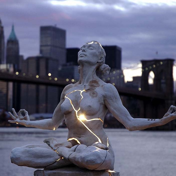 "Paige Bradley created this sculpture called ""Expansion"", a nude woman whose body split and emits light."