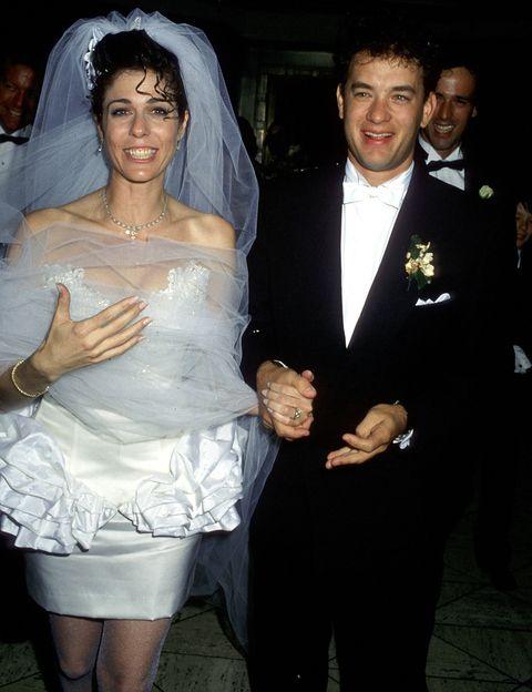 Corría el año 1988 y Rita Wilson luciría para su boda con el actor Tom Hanks un buen ejemplo de vestido ochentero: escote corazón, ceñido y corto, con volantes imposibles... Y ¡qué decir de esos rizos! 28 años después siguen casados en lo que ellos mismos han definido como un matrimonio difícil pero lleno de amor.
