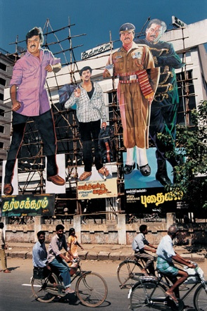 """'Bollywood Dreams' photographic series documents the vanishing world of old style Indian cinema. From website: """"Giant film cut-outs placed outside Padmam Theater in Chennai, India. The cut-outs, can be as high as 60 feet. These larger-than-life advertisements typically cost less to hand-paint than to print. In Southern India, particularly in Chennai and Hyderabad, hand-painted film advertisements like these still outnumber printed ones."""" Photo: Jonathan Torgovnik."""