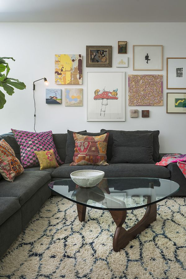 Patterned pillows and a gallery wall, along with a modern glass top coffee table and thick rug, give this living room an cozy, eclectic style.