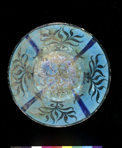 Fritware bowl with ring foot and straight sides that flare out slightly towards rim. Decorated with cobalt blue and black under a turquoise glaze. Interior of bowl has dark blue rim, and is divided into four panels by thick cobalt blue lines, each section filled with a waterweed design in underglaze black. Exterior of bowl is decorated with a few foliate sprigs in black under the turquoise . Place of origin: Iran (made) Jurjan, Latvia (recovered) Date: 1180-1220 (made) Museum number…
