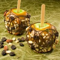 On The Trail Caramel Apples Recipe | Recipe4Living  I use candy corn or other cute Halloween color or themed candies.  Use your imagination! Fun project for scouts or kids craft time.