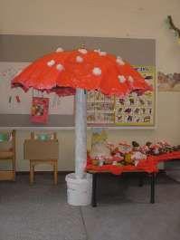 """reuzenpaddestoel gemaakt van parasol, de """"steel""""is in een grote kartonnen rol van vloerbedekking gedaan."""