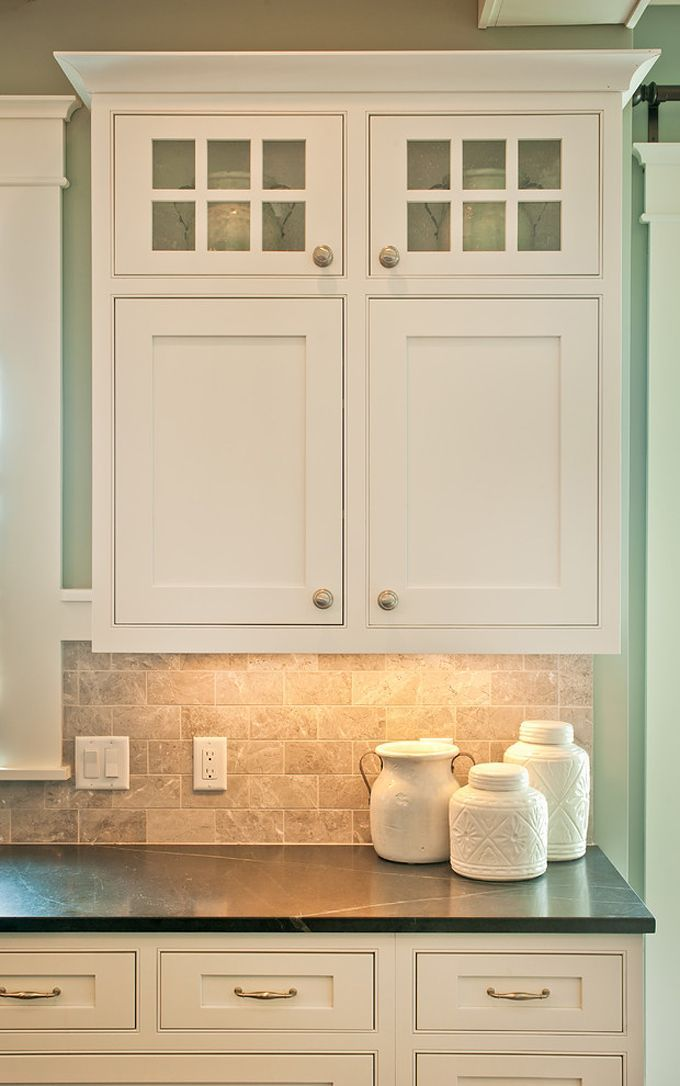 White cabinets with neutral stone backsplash and black countertops for a coastal kitchen vibe.