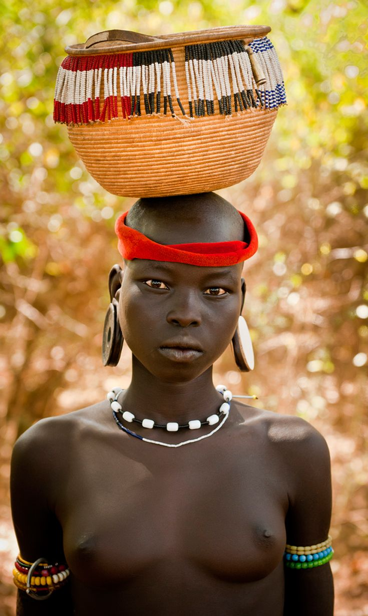 Africa. Mursi girl carrying a basket on her head. Omo Valley, Ethiopia. ©Gerry Andrews
