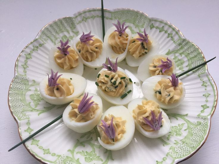 Quail Eggs a bit devilled. Filled with egg yolk, cream cheese, dijon mustard and chives. Garnished with fresh chive flowers. These little gems look delicate and elegant and are perfect for a platter of canapés.