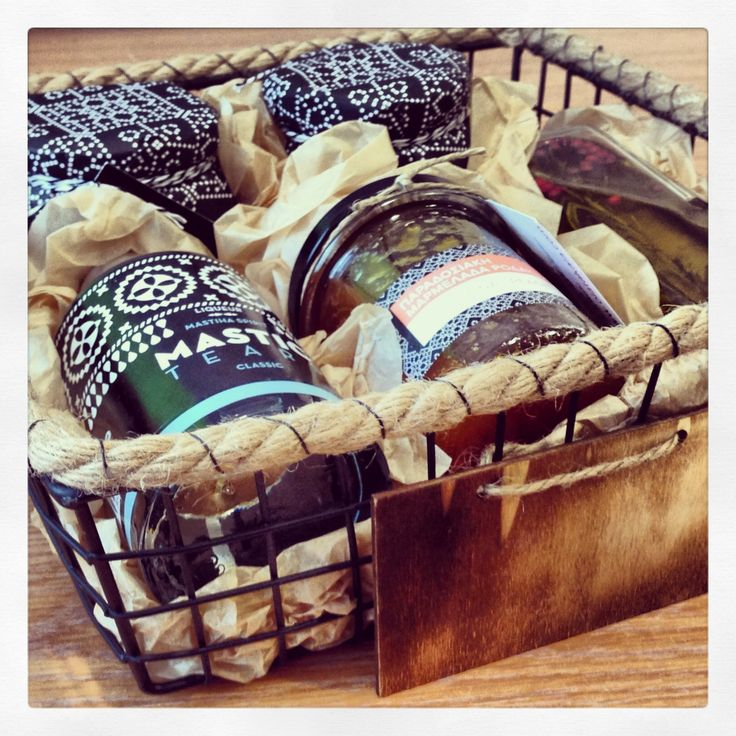 Square wire basket with rope detail on top and hanging wooden label, containing Mastic tears liqueur 200ml, extra virgin olive oil with herbs and whole pepper, home made peach jam from Kilkis and s...