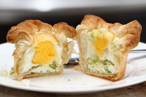 Eggs in a Basket  •2 small squares of puff pastry (big enough to fill the cavity of a muffin tin and have the corners stick out)   •2 eggs   •1 scallion   •some grated cheese   •salt, pepper   •a muffin tin   •butter or baking spray to grease the muffin tin