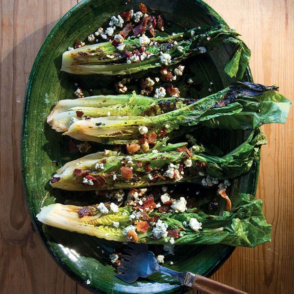 Fresh heads of romaine lettuce are split down the middle, grilled until charred and smoky, and then topped with blue cheese and bacon for this satisfying salad.