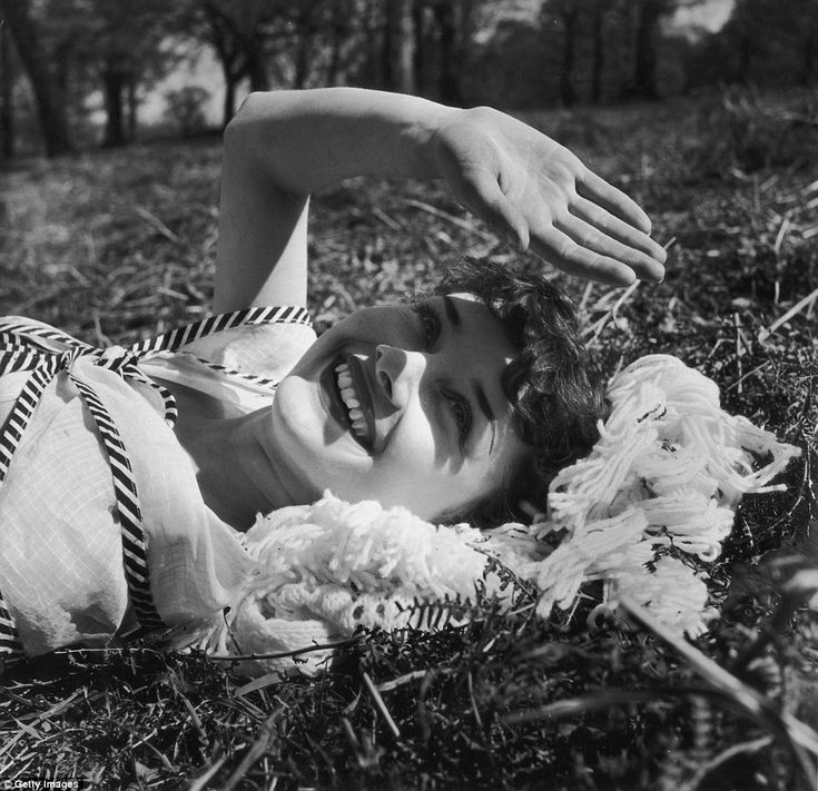 Flashing her iconic smile, Hepburn shields her face from the sun as she looks up from the ground towards the photographer