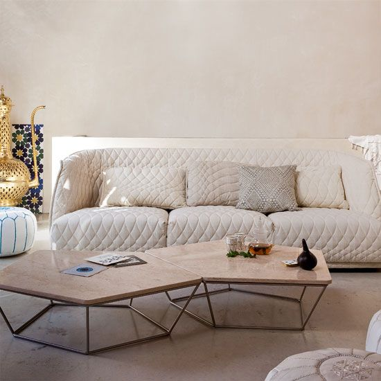 Neutral Moroccan living room with marble flooring, quilted sofa and marble table