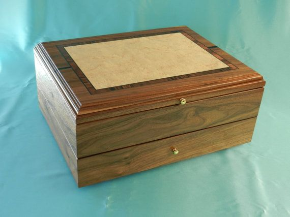This jewelry box is made from walnut and uses splined mitered joinery for strength and beauty. It has birds eye maple veneer on top of lid and is wrapped with Morado inlay banding with two pieces of gaboons ebony accent pieces. The profile of lid is cut with classical roman ogee cutter. Inside top level of box there are three equally divided compartments that are felt lined. Riding above the divided compartments are two sliding trays that are also divided into three sections and lined in…