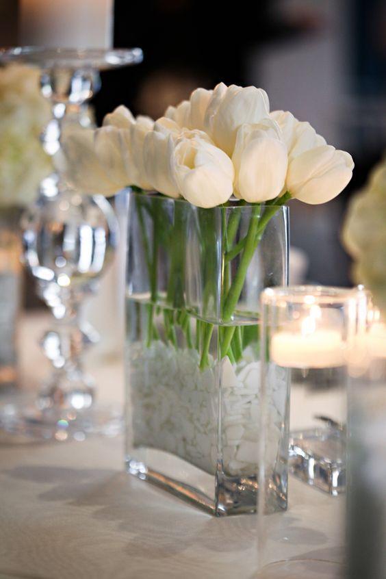 Weiße Tulpen wurden in einer rechteckigen Vase angeordnet, umgeben von schwimmenden Kerzen