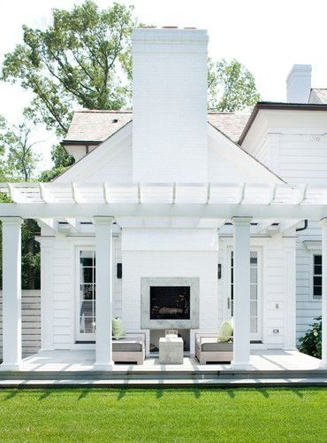 Love this all-white pergola next to a modern Colonial-style home, complete with an outdoor fireplace.